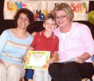 The Graduate with his diploma & teachers (Mrs. Isabelle & Mrs. Angela